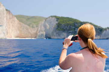 Woman takes a photograph of Navagio (Shipwreck) Bay from a boat