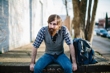 A hipster with a backpack sitting in an urban setting