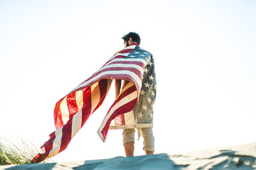 Low angle view of a man wrapped in American flag standing against sky