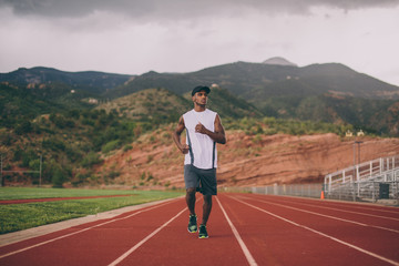 Black guy in a hat jogging on a track