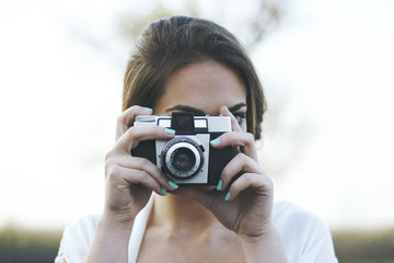 Young woman photographing with an old camera