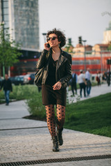 Young woman on the phone walking in the business district