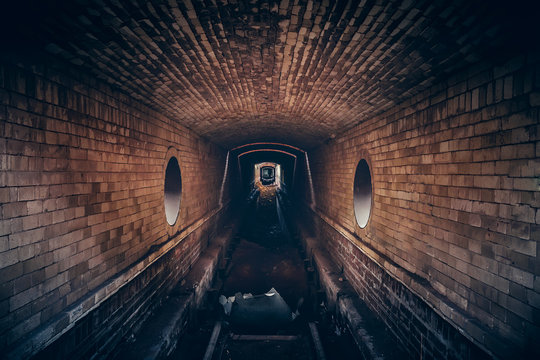 Red brick underground sewer tunnel with dramatic mysterious atmosphere