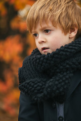 A portrait of a young boy in a big scarf looking away