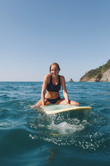 Woman sitting on her surfboard floating in the ocean while waiting for the next wave to come