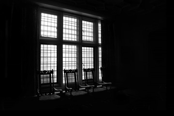 silhouette of chairs against a window in a dark room
