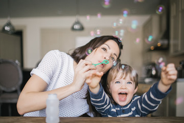 Mom blowing bubbles with her laughing son
