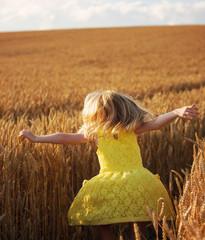 A little girl dancing in a field of wheat