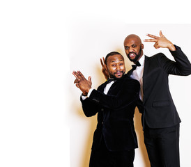 two afro-american businessmen in black suits emotional posing, gesturing, smiling. wearing bow-ties closeup