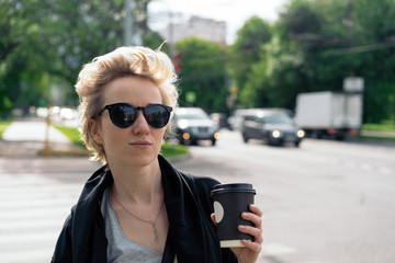 the girl drinks coffee on the road