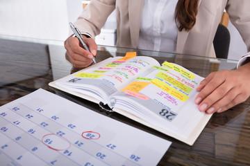 Fototapete - Businesswoman Making Agenda On Diary