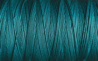Close up spool of blue cotton thread