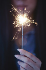 Close up of hands of a woman holding sparkler.
