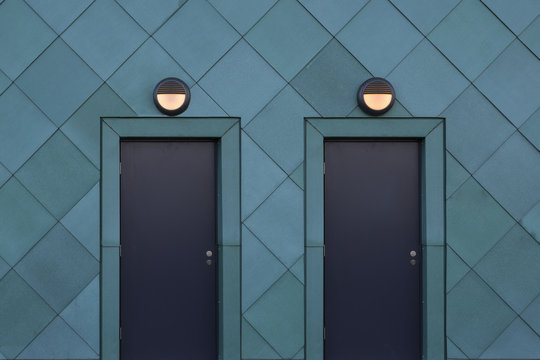Two matching metal doors with lights above in a green metal-clad building