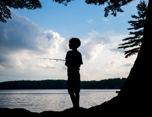 Silhouette of a boy fishing on a lake at sunset