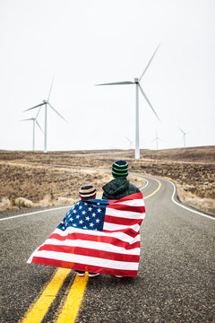 Two little boys with American flag standing near wind farm