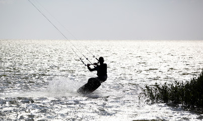 Kitesurfer in action, silhouetted against the bright water