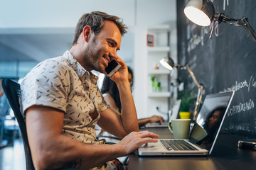 Happy Man Working on Laptop at the Office while Talking on Phone