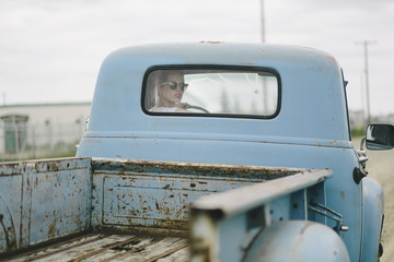 Blond girl driving an old pickup truck