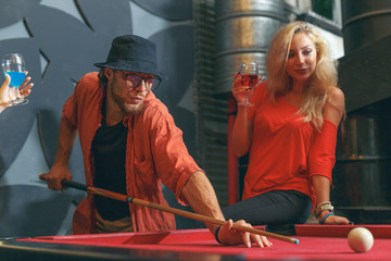 Young happy friends playing pool at billiards table together, friendship, party and nightclub concept