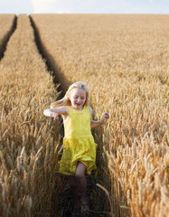 A female child running thought a field of wheat