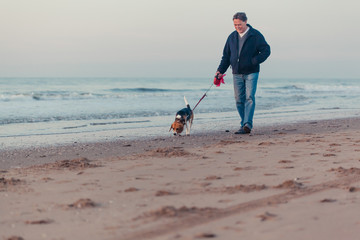 Older man walking on the beach with a beagle dog on a leash