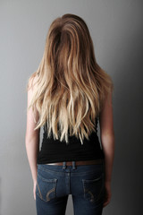 Backside of teenager with long hair wearing jeans and black tank top