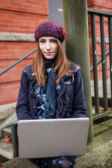 Female college student studying on campus using her laptop