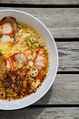 Closeup spicy egg noodle soup on wood background