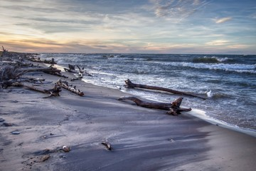 Summer Evening Beach Background. Remote beach with driftwood and waves crashing on the shore. Shot at twilight in horizontal orientation with copy space in the foreground. Whitefish Point, Michigan.