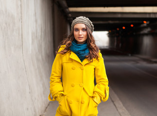 Woman in Yellow Coat Standing Near the Tunnel