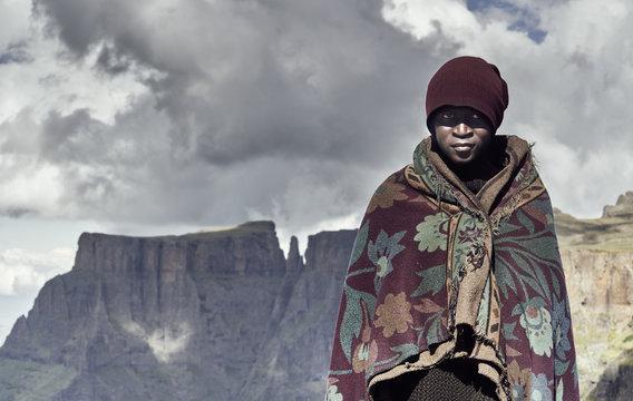 A portrait of a black Basotho shepherd wrapped in a traditional blanket.