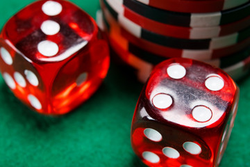 two red dice cubes, lie on a green table