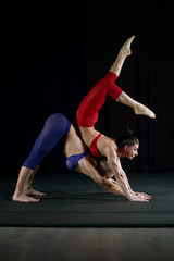 Two girls doing acrobatics in the sports Studio . Gymnastic yoga