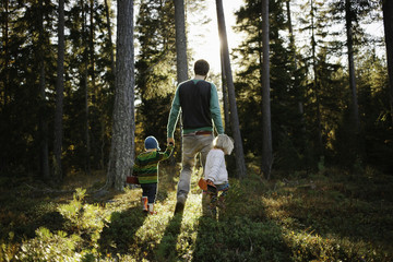 Young family walking through the forest in Sweden.