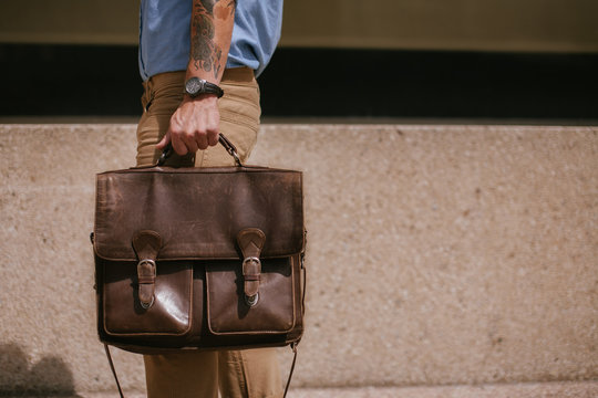 Young man walking downtown with briefcase