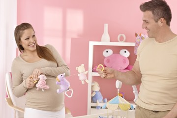 Young couple preparing baby's room