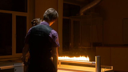 Students look at the flame in the lab. Students conduct an experiment