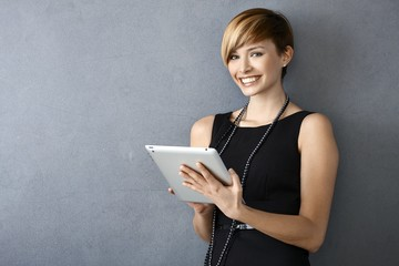 Elegant young woman using tablet leaning to wall