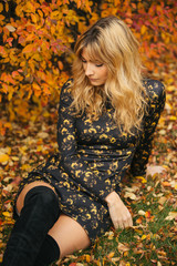 A beautiful blonde sitting down relaxing on a fall day looking down