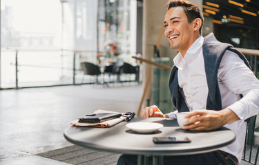 Smiling businessman working from a coffeeshop