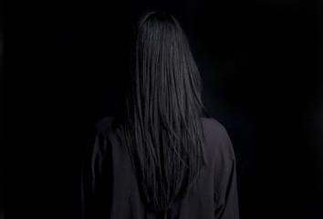 Capelli lunghi e neri su sfondo nero