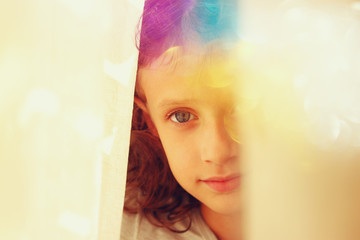 abstract portrait of thoughtful little girl near window. vintage filtered image