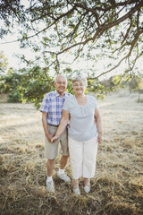 Cute elderly couple smiling together outside