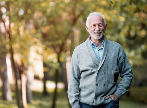 Elderly man smiling outdoors in nature
