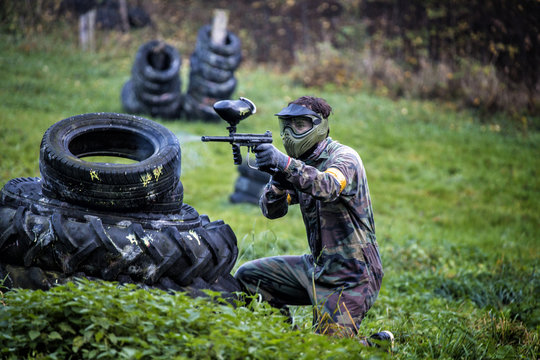 Paintball player aiming and hiding