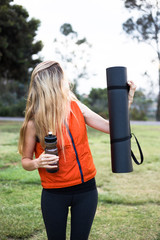 blonde woman hold black yoga mat and botle of water on the grass
