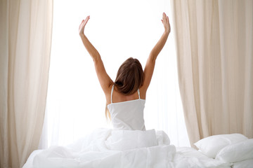 Woman stretching in bed after wake up, back view, entering a day happy and relaxed after good night sleep. Sweet dreams, good morning, new day, weekend, holidays concept
