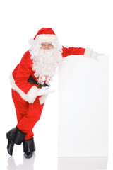 Santa Claus pointing on blank white wall, advertisement banner with copy space. Isolated on white background. Full length portrait