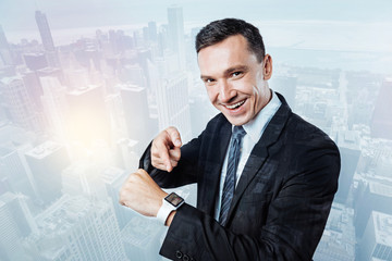 Cheerful happy businessman pointing at his watch